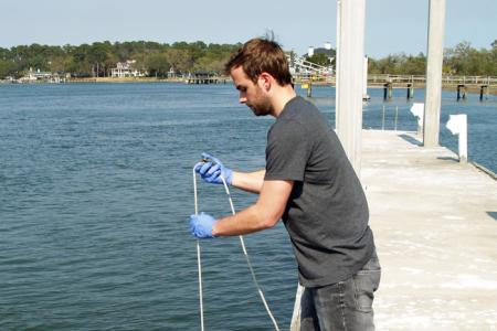 UGA Skidaway Institute grad student Sean Anderson collects a water sample from the Skidaway River.